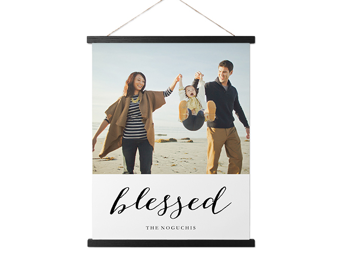 "A hanging canvas print with a family photo and the word ""blessed."""